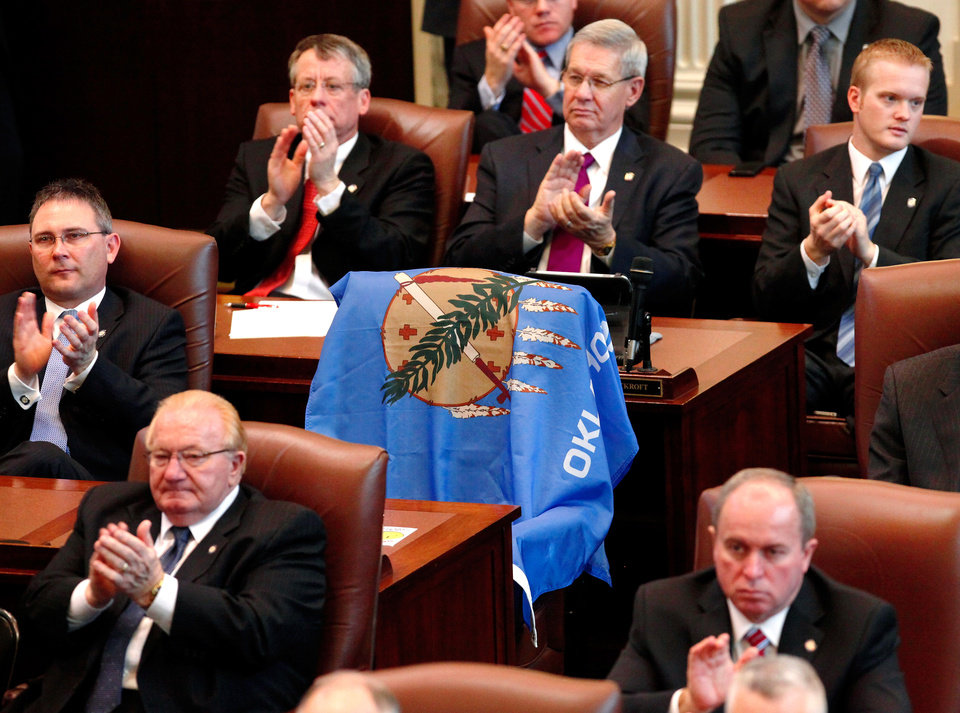 Photo - This unoccupied chair, once the seat of deceased  Rep. Rusty Farley of Idabel, was draped with an Oklahoma flag and surrounded by other state lawmakers as  Gov. Mary Fallin delivered her 2012 State of the State address to a joint session of the Oklahoma legislature in the House Chamber  Monday, Feb, 6, 2012. Farley died last summer while the legislature was out of session.   Photo by Jim Beckel, The Oklahoman