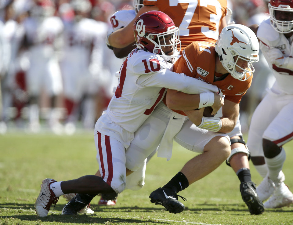 Photo - Oklahoma safety Pat Fields (10) brings down Texas quarterback Sam Ehlinger (11) during the Red River Showdown college football game between the University of Oklahoma Sooners (OU) and the Texas Longhorns (UT) at Cotton Bowl Stadium in Dallas, Saturday, Oct. 12, 2019. Oklahoma won 34-27. [Bryan Terry/The Oklahoman]