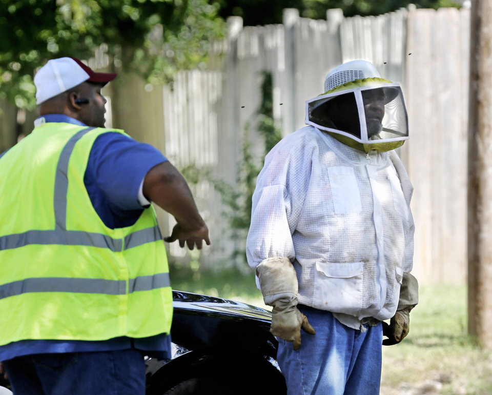 Photo - A city worker swats at bees that can be seen flying around the head of a co-worker during bee attack. Worker at right is wearing protective helmet with netting loaned to him by Forest Chapman, a beekeeper and community outreach coordinator with the Oklahoma State Beekeepers Association.  Without warning, thousands of bees began swarming and stinging city crews Wednesday morning, Sep. 19, 2018, while they were picking up brush and trees in a residential area south of the downtown area. Just before 11 a.m., debris removal crews working near SE 23 and Walnut Avenue used a grappling arm to pick up a large, hollowed-out tree and set it in the back of a dump truck. One of the workers was stung about 15 times and the other man just a couple as they both raced to the safety of the cab of their city truck, said Capt. David Macy, spokesman for the Oklahoma City Fire Department.  Photo by Jim Beckel, The Oklahoman