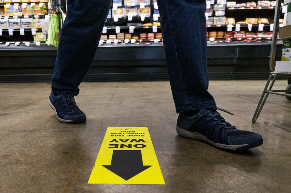 Photo - A customer follows the shopping flow arrow in an aisle at the Homeland located at 1108 NW 18th St. in Oklahoma City, Okla. on Monday, April 13, 2020. The store has taken extra steps to help protect its employees and customers during the coronavirus pandemic.   [Chris Landsberger/The Oklahoman]