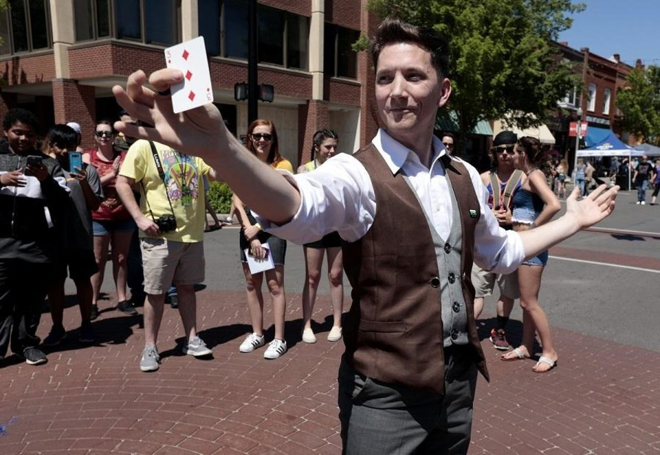 Photo - Magician Joe Coover performs a magic show in the street during Norman Music Fest 2019 on April 27, 2019 in Norman, Okla. For the second year, Coover will be among the performers at the Opening Night New Year's Eve celebration in downtown Oklahoma City. [The Oklahoman Archives]