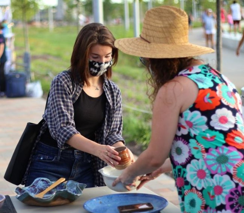 Photo -  Haley Korff looks at pottery as Melissa Cobbs Leon, of H&M Pottery, on July 31 at the Night Market at Scissortail Park in downtown Oklahoma City. [Doug Hoke/The Oklahoman Archives]