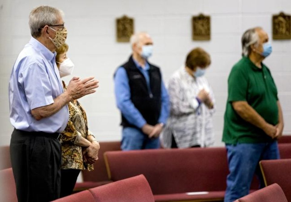 Photo -  James Spencer, left, prays with other parishioners at Holy Spirit Catholic Church in Mustang. [Chris Landsberger/The Oklahoman]