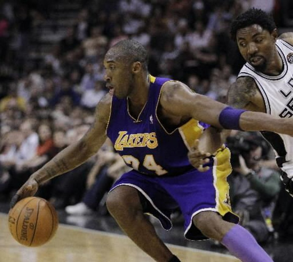Photo - Los Angeles Lakers'  Kobe   Bryant, left, is defended by San Antonio Spurs' Roger Mason, Jr. during the fourth quarter of an NBA basketball game, Wednesday, March 24, 2010 in San Antonio. Los Angeles won 92-83. (AP Photo/Eric Gay)