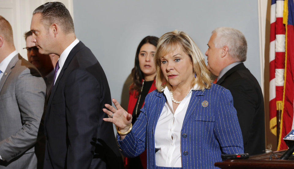 Photo - Gov. Mary Fallin deflects a reporter's question as she and lawmakers leave the Blue Room at the end of a news conference Monday morning, Oct. 23, 2017. Speaker of the House Charles McCall, left, and Senate President pro-tempore Mike Schulz, right, accompany the governor out of the room. The governor announced at the media briefing that she and Republican leadership have endorsed a revenue package that would prevent cuts to Oklahoma's major health care agencies and boost teacher salaries, but the proposal needs Democratic support to pass the Oklahoma House. Photo by Jim Beckel, The Oklahoman