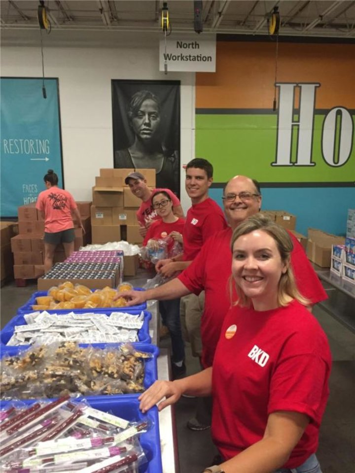 Photo -  BKD employees pack food at the Regional Food Bank of Oklahoma. [Photo provided]
