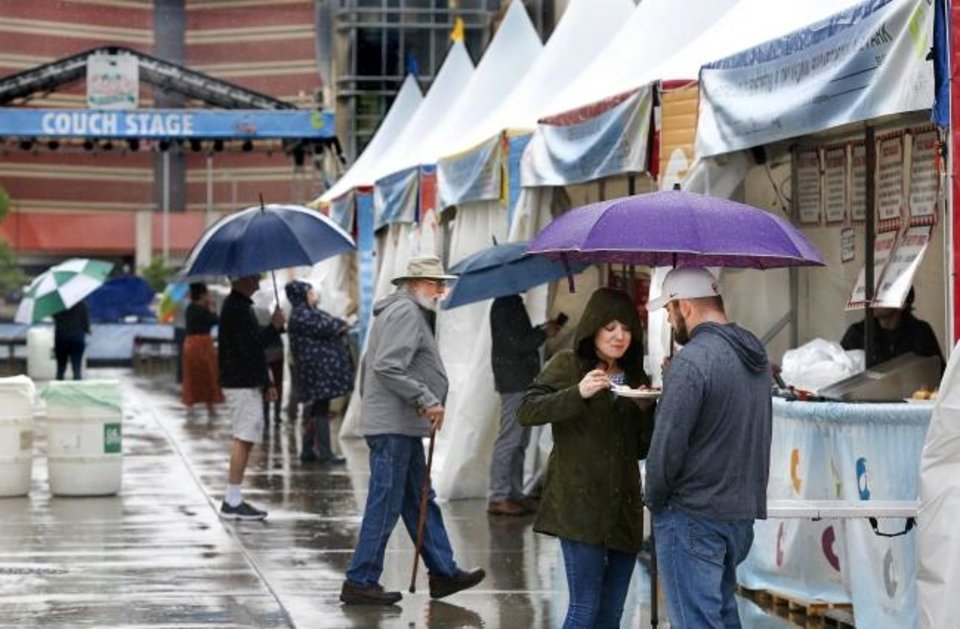 Photo -  Katie Lentz and Jess Powell, of Norman, share an umbrella and a plate of food on the opening day of the Festival of the Arts in downtown Oklahoma City. [JIM BECKEL/THE OKLAHOMAN]
