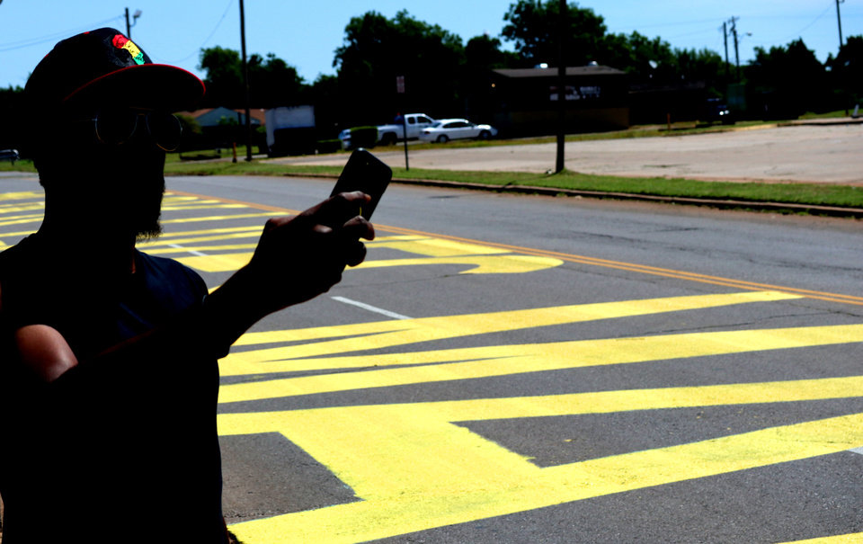 Photo - A man takes video of the Black Lives Matter! that was painted on the west bound lanes of Springlake Dr., just east of the intersection of NE 36th and Kelley Ave.,Wednesday, June 24, 2020. [Doug Hoke/The Oklahoman]
