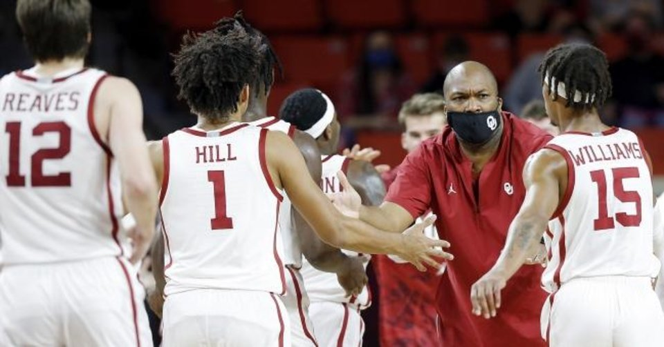 Photo -  Oklahoma assistant coach Carlin Hartman, who is in his fifth season with the Sooners, slaps hands with his team during a game earlier this season. He has never been a head coach. [Ty Russell/SoonerSports.com]