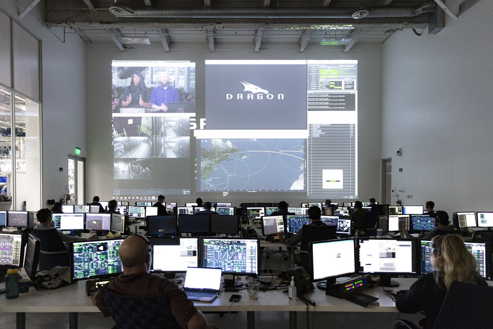 Photo -  In this Thursday, March 19, 2020 photo made available by SpaceX, SpaceX teams in Firing Room 4 at NASA's Kennedy Space Center in Cape Canaveral, Fla., work with the company's Mission Control in Hawthorne, Calif., along with NASA flight controllers in Mission Control Houston, on a full simulation of launch and docking of the Crew Dragon spacecraft, with NASA astronauts Bob Behnken and Doug Hurley participating in SpaceX's flight simulator. (SpaceX via AP)