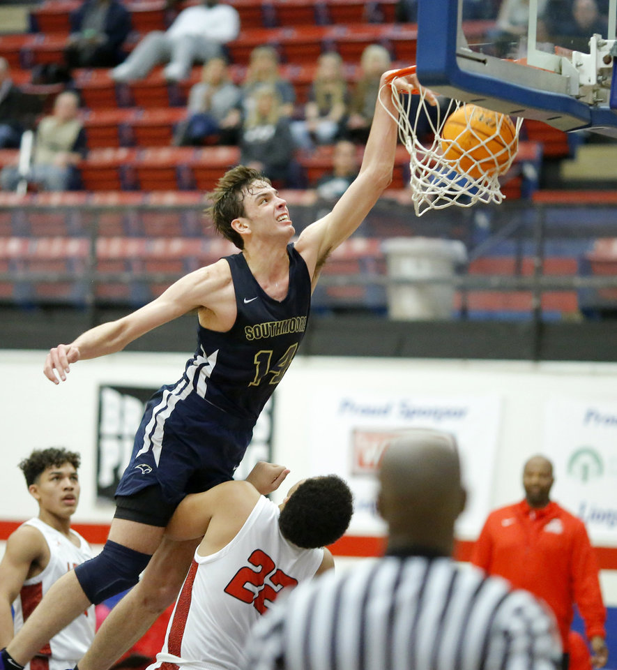Photo - Southmoore's Sam Godwin is called for a charge as he dunks over Lawton's Eric Wiley during a boys basketball game between Southmoore and Lawton in Moore, Okla., Friday, Jan. 24, 2020. [Bryan Terry/The Oklahoman]
