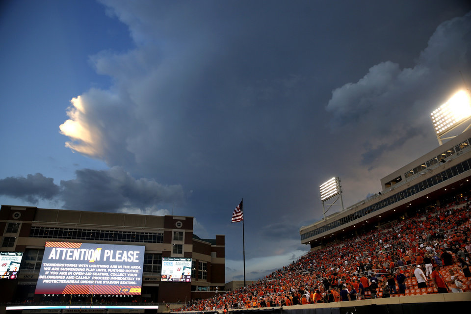 Photo - Storm clouds build behind Boone Pickens Stadium during a weather delay during the college football game between the Oklahoma State Cowboys and the Kansas State Wildcats at Boone Pickens Stadium in Stillwater, Okla., Saturday, Sept. 28, 2019. [Sarah Phipps/The Oklahoman]