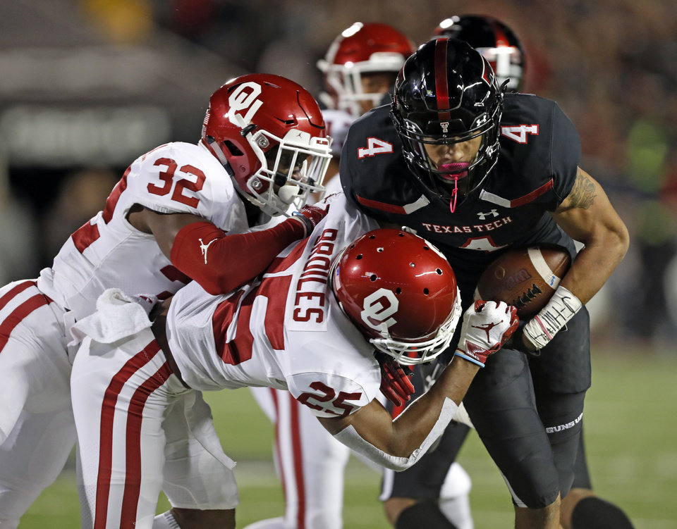 Photo - Texas Tech's Antoine Wesley (4) is tackled by Oklahoma's Justin Broiles (25) and Delarrin Turner-Yell (32) during the first half of an NCAA college football game Saturday, Nov. 3, 2018, in Lubbock, Texas. (AP Photo/Brad Tollefson)