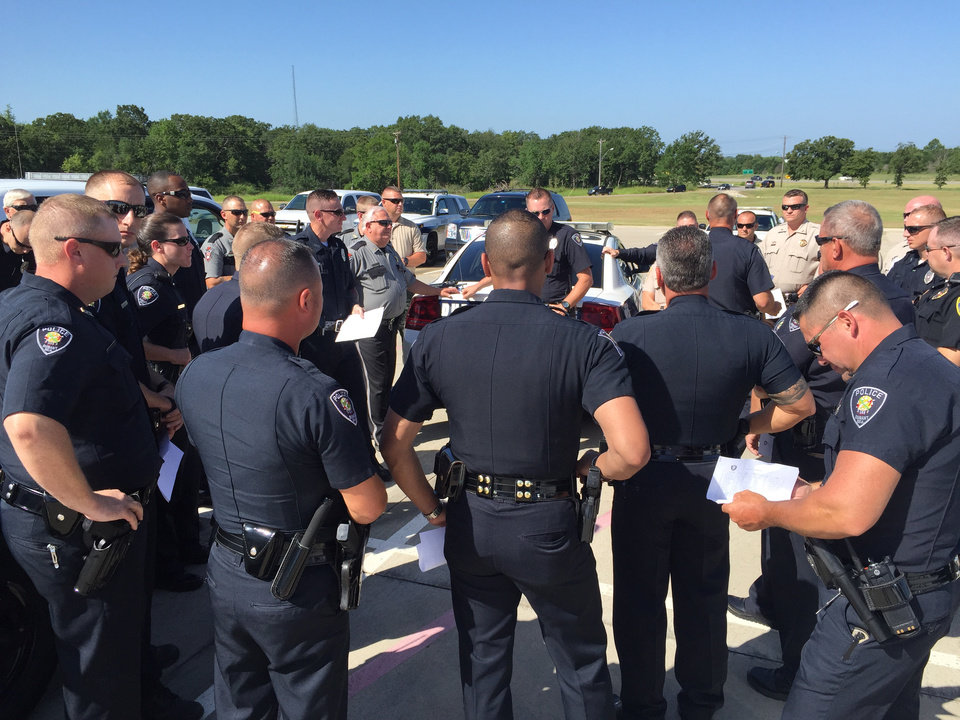 Photo - Durant police officers gather in parking lot of Durant High School Wednesday morning to receive final assignments pertaining to President Obama's visit to their community later this afternoon. Photo by Jim Beckel