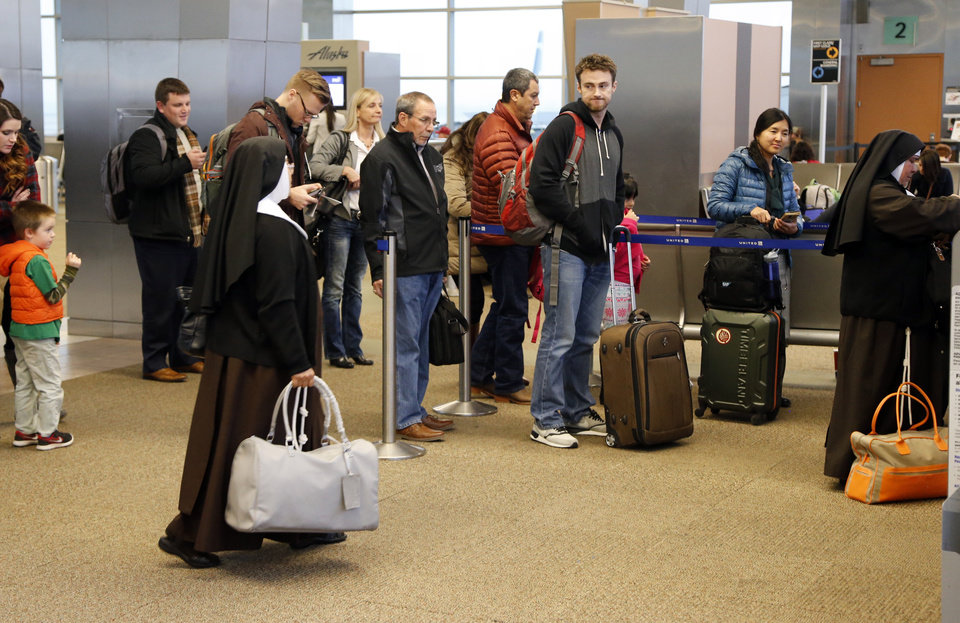 Photo -  Travelers line up to board a plane Thursday at Will Rogers World Airport. [Photo by Steve Sisney, The Oklahoman]