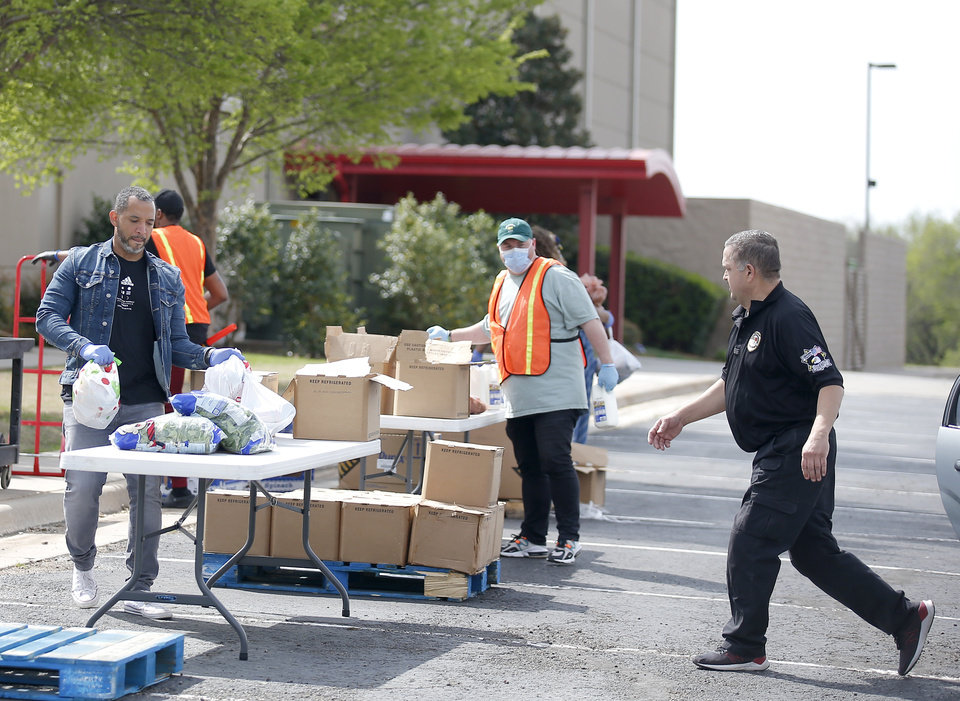 Photo - People load food into cars at PeopleÕs Church, 800 E. Britton Rd., in Oklahoma City, Thursday, April 9, 2020. Cars lined up for miles for hours as the church members gave away 6,000 pounds of free groceries and supplies. [Sarah Phipps/The Oklahoman]