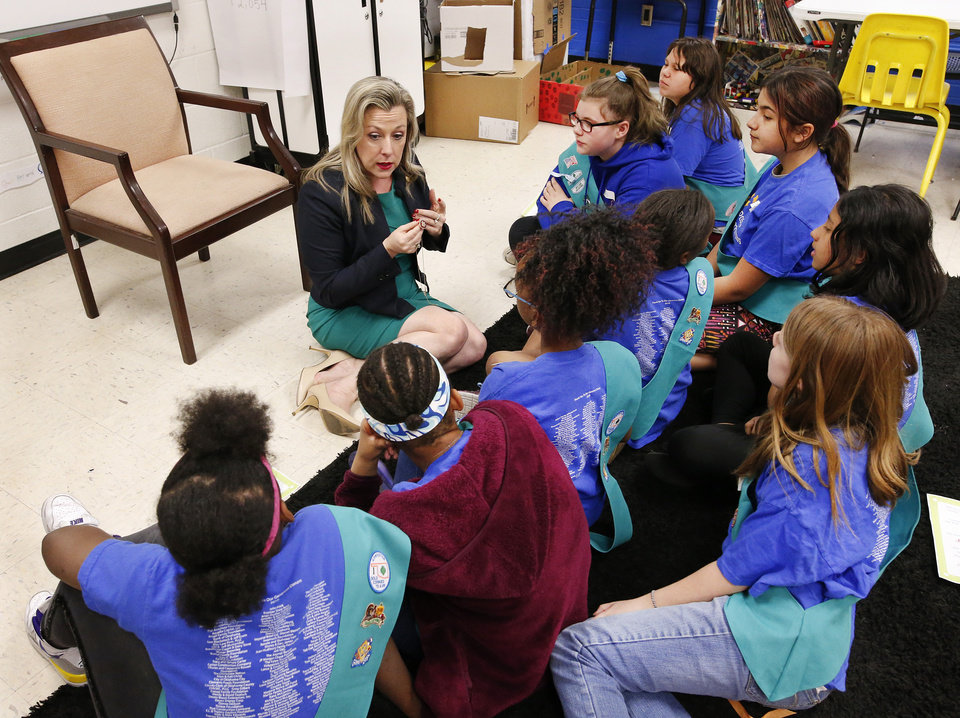 Photo - U. S. Rep. Kendra Horn shows students the pin issued to her to signify she is a member of the House of Representatives. Many members wear the pin on the lapel of their coat but she showed the girls how she put a chain on hers and usually wears it like a necklace around her neck. Horn visits a Girl Scout troop on Monday afternoon, April 15, 2019, at Positive Tomorrow School, a school dedicated to educating homeless students in Oklahoma City.    Photo by Jim Beckel, The Oklahoman.