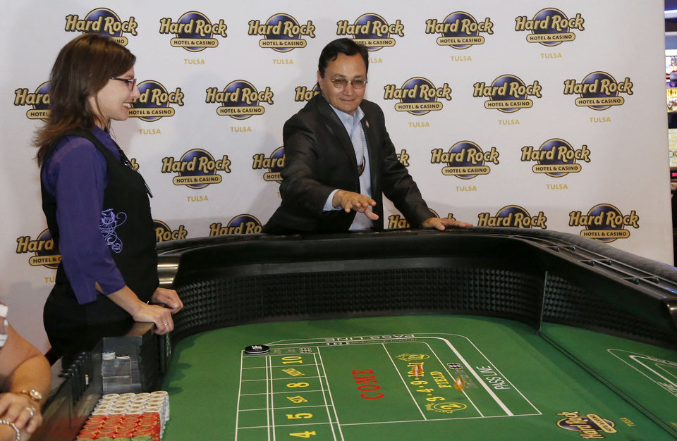 Photo -  Cherokee Nation Secretary of State Chuck Hoskin Jr. throws the first dice Monday on the craps table in Tulsa with dealer Marianna Smith during the first day that Okahoma casinos are able to use ball and dice. [PHOTOS BY STEPHEN PINGRY, TULSA WORLD]