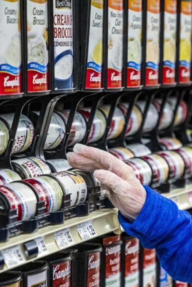 Photo -  Customer Shirley Lee wears gloves while shopping at the Homeland at 11241 W Reno. [Chris Landsberger/The Oklahoman]