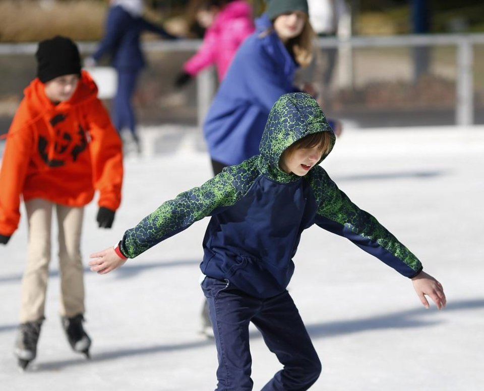 Photo - Finley Cunningham, foreground, skates with classmates. Middle-school students from John Rex School enjoyed ice skating on the Devon Ice Rink in the Myriad Gardens Friday morning, Nov. 9, 2018. [The Oklahoman Archives]