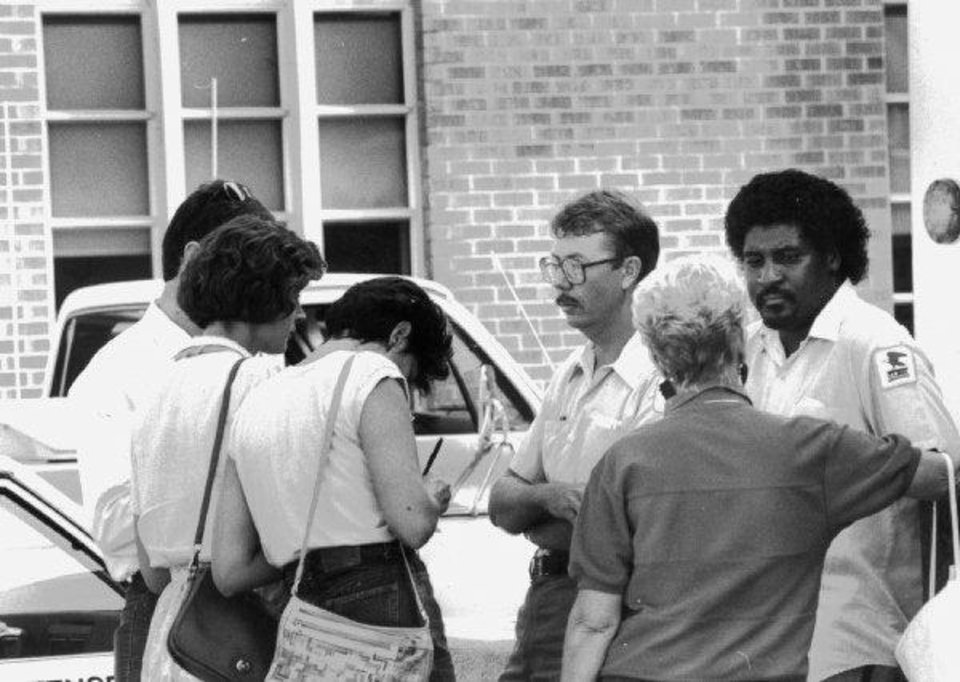 Photo - MURDER: Edmond Post Office Massacre: Reporters interview two workers outside the Edmond Post Office and the mass murders. 8/20/1979