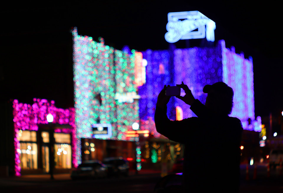 Photo -  A man photographs Lights on Broadway, Automobile Alley's holiday lights. [Photo by Doug Hoke, The Oklahoman]