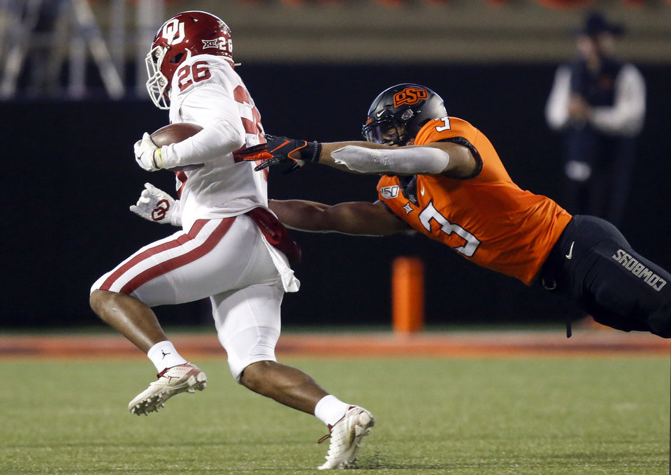 Photo - Oklahoma's Kennedy Brooks (26) gets away from Oklahoma State's Tre Sterling (3) as he carries the ball during the Bedlam college football game between the Oklahoma State Cowboys (OSU) and Oklahoma Sooners (OU) at Boone Pickens Stadium in Stillwater, Okla., Saturday, Nov. 30, 2019. [Nate Billings/The Oklahoman]
