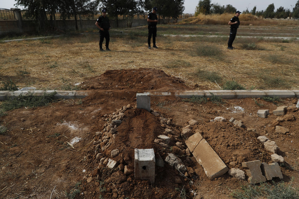 Photo -  Turkish police officers secure the area of the cemetery where the grave of ten-month-old Mohammed Omar Saar, killed during incoming shelling from Syria Thursday, is following the funeral in Akcakale, Sanliurfa province, southeastern Turkey, at the border with Syria, Friday, Oct. 11, 2019. (AP Photo/Lefteris Pitarakis)