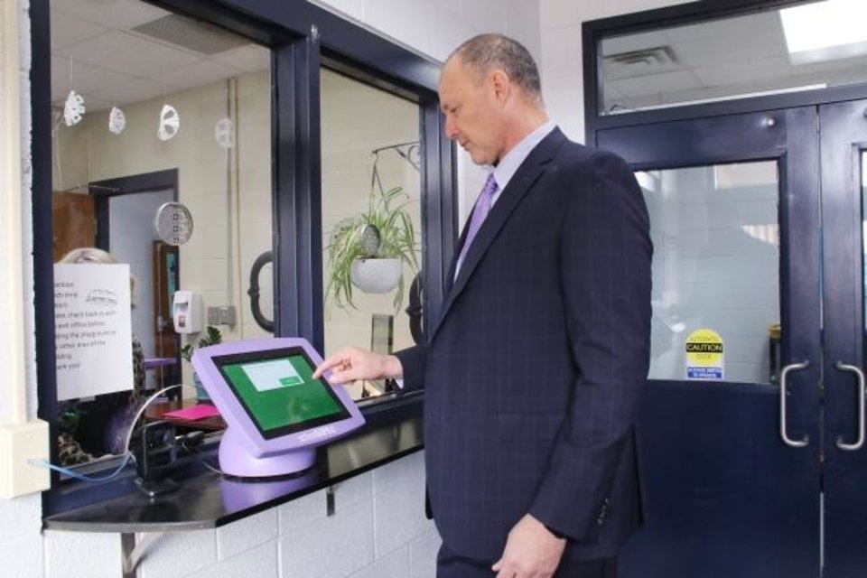 Photo -  Bethany Superintendent Drew Eichelberger tests the electronic security kiosk inside a school vestibule where visitors are required to check in. [PHOTO PROVIDED]
