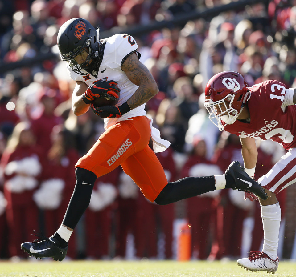 Photo - Oklahoma State's Tylan Wallace (2) makes a catch for a long gain in front of Oklahoma's Tre Norwood (13) during a Bedlam college football game between the University of Oklahoma Sooners (OU) and the Oklahoma State University Cowboys (OSU) at Gaylord Family-Oklahoma Memorial Stadium in Norman, Okla., Nov. 10, 2018. Photo by Nate Billings, The Oklahoman