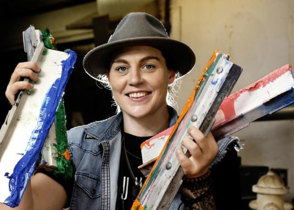 Photo -  Haley Griffin shows some of the tools of her clothing creation trade in her southwest Oklahoma City business.