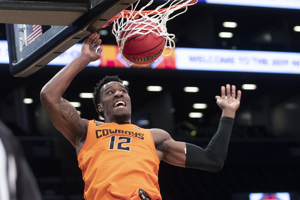 Photo -  Oklahoma State forward Cameron McGriff dunks in two of his team-high 15 points Friday in a 78-37 win against Ole Miss in New York. [AP Photo/Mary Altaffer]