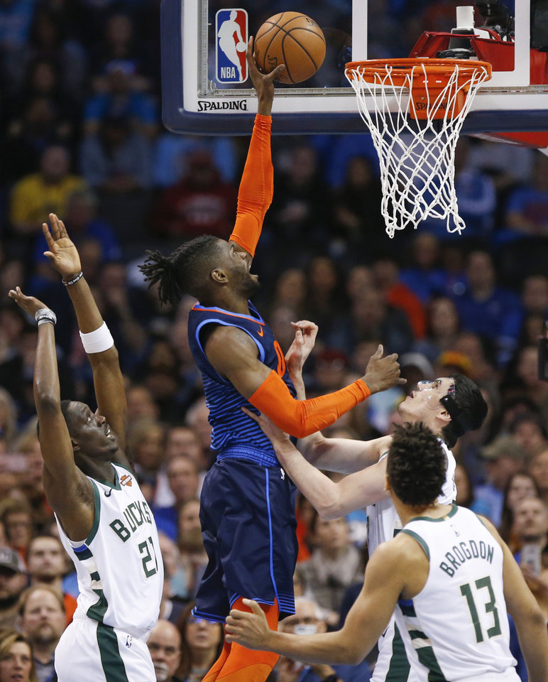 Photo - Oklahoma City's Nerlens Noel (3) shoots between Milwaukee's Tony Snell (21), Ersan Ilyasova (77) and Malcolm Brogdon (13) during an NBA basketball game between the Milwaukee Bucks and the Oklahoma City Thunder at Chesapeake Energy Arena in Oklahoma City, Sunday, Jan. 27, 2019. Photo by Nate Billings, The Oklahoman