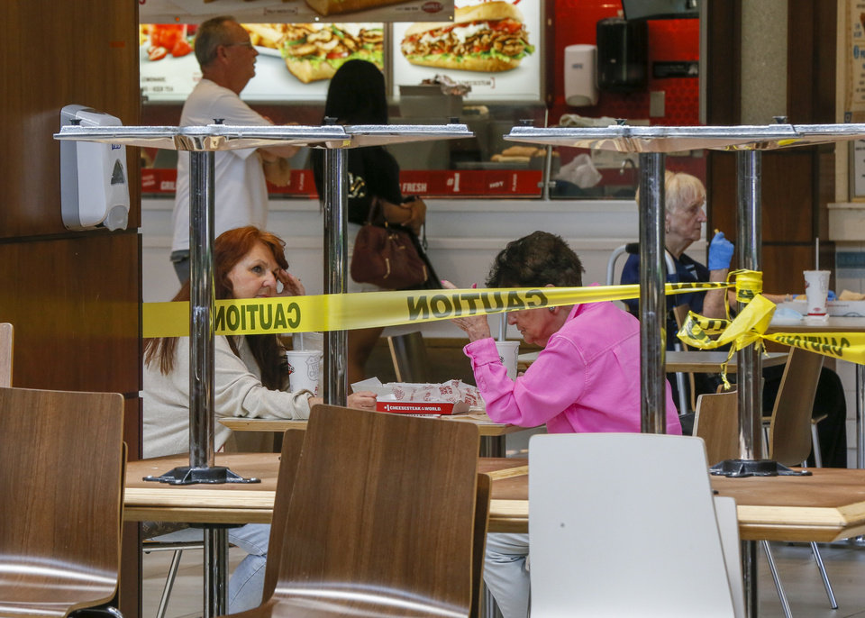 Photo - People in the food court are framed by tables and chairs that are put away to limit the seating at Penn Square Mall during the re-opening of the mall after being closed because of the coronavirus pandemic, in Oklahoma City, Friday, May 1, 2020. [Nate Billings/The Oklahoman]