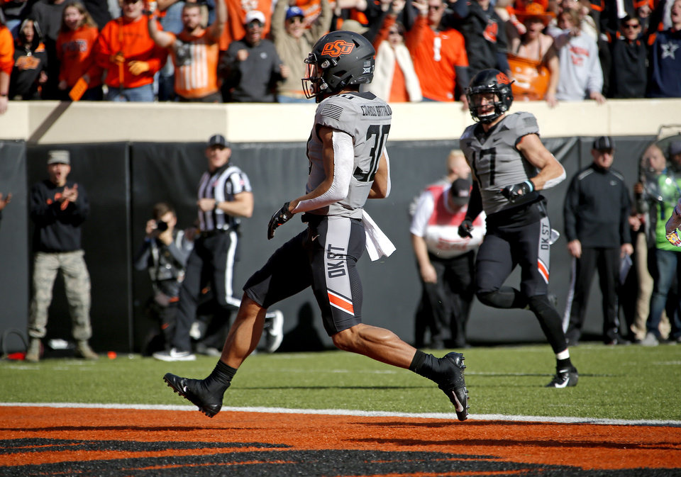 Photo - Oklahoma State's Chuba Hubbard (30) scores a touchdown in the first quarter during the college football game between the Oklahoma State University Cowboys and the Kansas Jayhawks at Boone Pickens Stadium in Stillwater, Okla., Saturday, Nov. 16, 2019. OSU won 31-13. [Sarah Phipps/The Oklahoman]