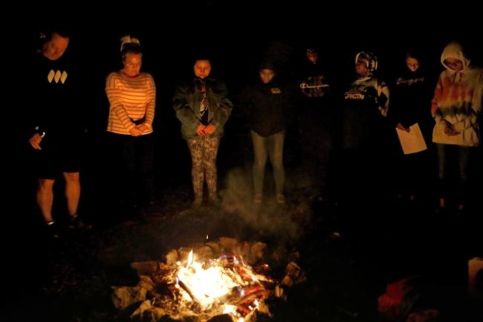 Photo -  Youth and mentors pray around a campfire during an outdoors class. [Sarah Phipps/The Oklahoman]