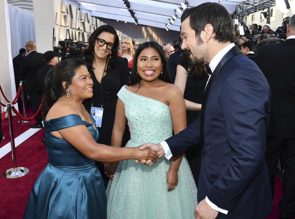 Photo -  Margarita Martinez Merino, left, shakes hands with Diego Luna, right, as Yalitza Aparicio looks on during arrivals at the Oscars on Sunday, Feb. 24, 2019, at the Dolby Theatre in Los Angeles. (Photo by Charles Sykes/Invision/AP)