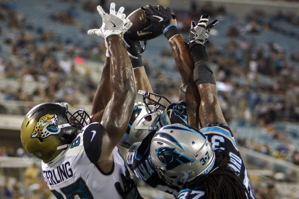Photo -  Del City native Jeff Richards, center, intercepts a 2-point conversion pass intended for Jacksonville Jaguars tight end Neal Sterling (87) as Carolina safety Dezmen Southward (37) comes in to help during a preseason game in late August. [AP PHOTO]