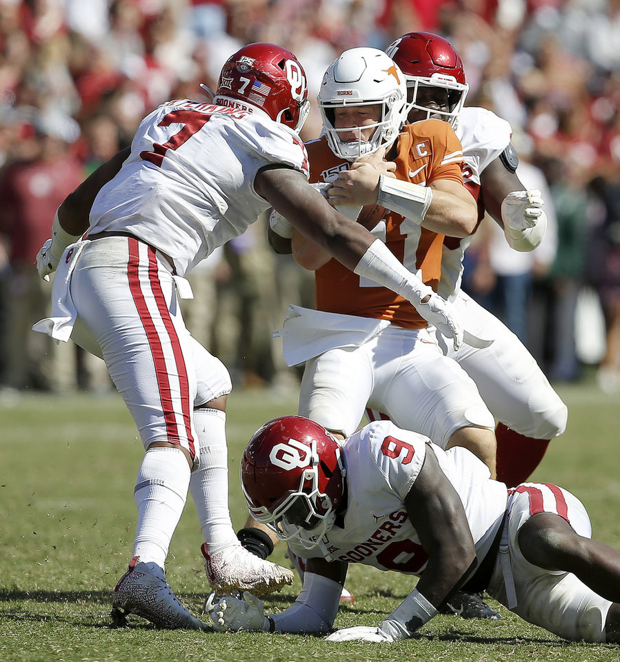 Photo - Oklahoma's Ronnie Perkins (7), Neville Gallimore (90) and Kenneth Murray (9) bring down Texas quarterback Sam Ehlinger (11) during the Red River Showdown college football game between the University of Oklahoma Sooners (OU) and the Texas Longhorns (UT) at Cotton Bowl Stadium in Dallas, Saturday, Oct. 12, 2019. Oklahoma won 34-27. [Bryan Terry/The Oklahoman]