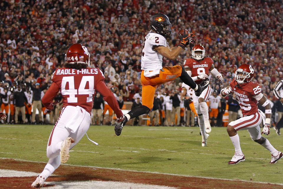 Photo - Oklahoma State's Tylan Wallace (2) catches a touchdown pass between Oklahoma's Brendan Radley-Hiles (44), Kenneth Murray (9) and Justin Broiles (25) late in the forth quarter of a Bedlam college football game between the University of Oklahoma Sooners (OU) and the Oklahoma State University Cowboys (OSU) at Gaylord Family-Oklahoma Memorial Stadium in Norman, Okla., Nov. 10, 2018.  Photo by Bryan Terry, The Oklahoman