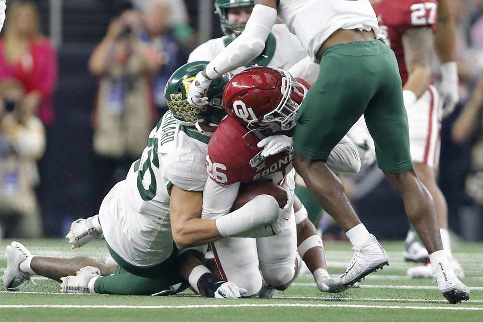 Photo - Oklahoma's Kennedy Brooks (26) is injured as he is brought down during the Big 12 Championship Game between the University of Oklahoma Sooners (OU) and the Baylor University Bears at AT&T Stadium in Arlington, Texas, Saturday, Dec. 7, 2019. Oklahoma won 30-23. [Bryan Terry/The Oklahoman]