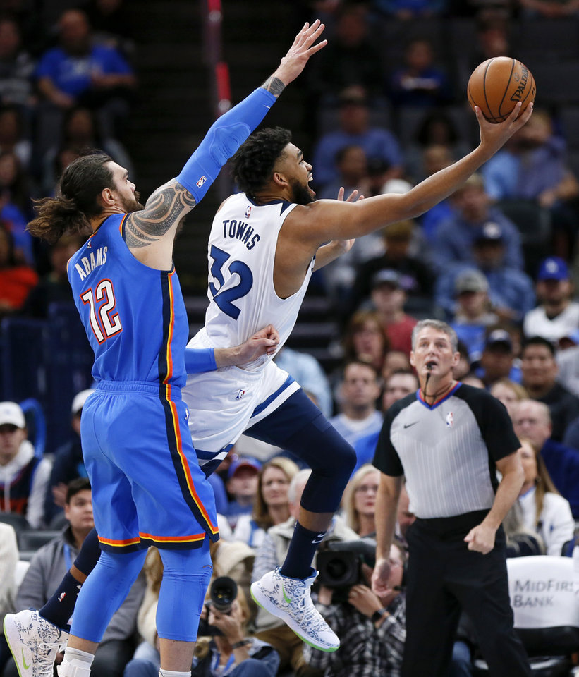Photo - Minnesota's Karl-Anthony Towns (32) shoots in front of Oklahoma City's Steven Adams (12) in the first quarter during an NBA basketball game between the Minnesota Timberwolves and the Oklahoma City Thunder at Chesapeake Energy Arena in Oklahoma City, Friday, Dec. 6, 2019. [Nate Billings/The Oklahoman]