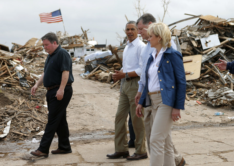 Photo - President Barack Obama walks towards Plaza Towers Elementary School in Moore, Okla.,with Moore Mayor Glenn Lewis, left, U.S. Rep Tom Cole, and Gov. Mary Fallin, Sunday, May 26, 2013. President Obama toured the area in Moore that was hit by a tornado on May, 20, 2013.  Photo by Bryan Terry, The Oklahoman ORG XMIT: OKC1305261411038212