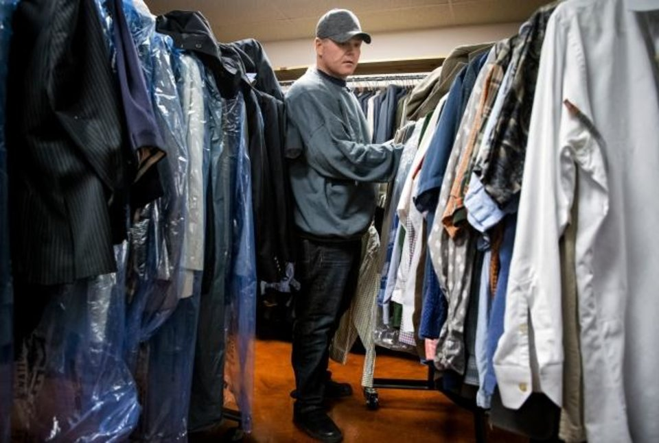 Photo - Warren Rawls, who was released from prison through commutation on Monday, picks out some clothing at The Education and Employment Ministry (TEEM) office in Oklahoma City, Okla. on Tuesday, Nov. 5, 2019. TEEM and other area nonprofit groups and community partners are working to help people who were released through Monday's commutation make the transition to life outside of prison.      [Chris Landsberger/The Oklahoman]