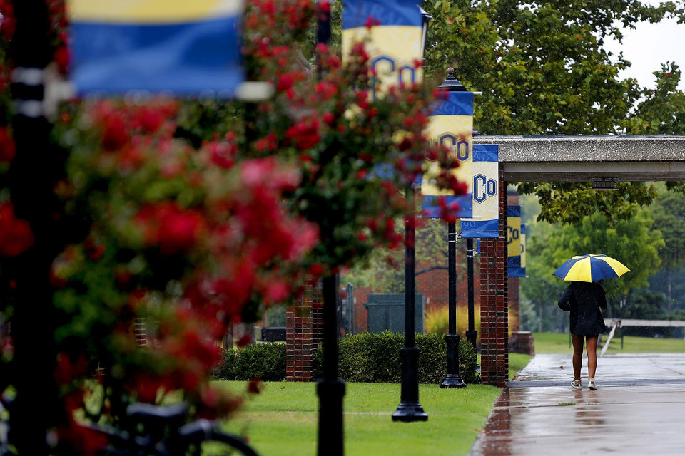 Photo -  A person walks with the umbrella in the rain across the University of Central Oklahoma campus in Edmond. [Bryan Terry/The Oklahoman archives]