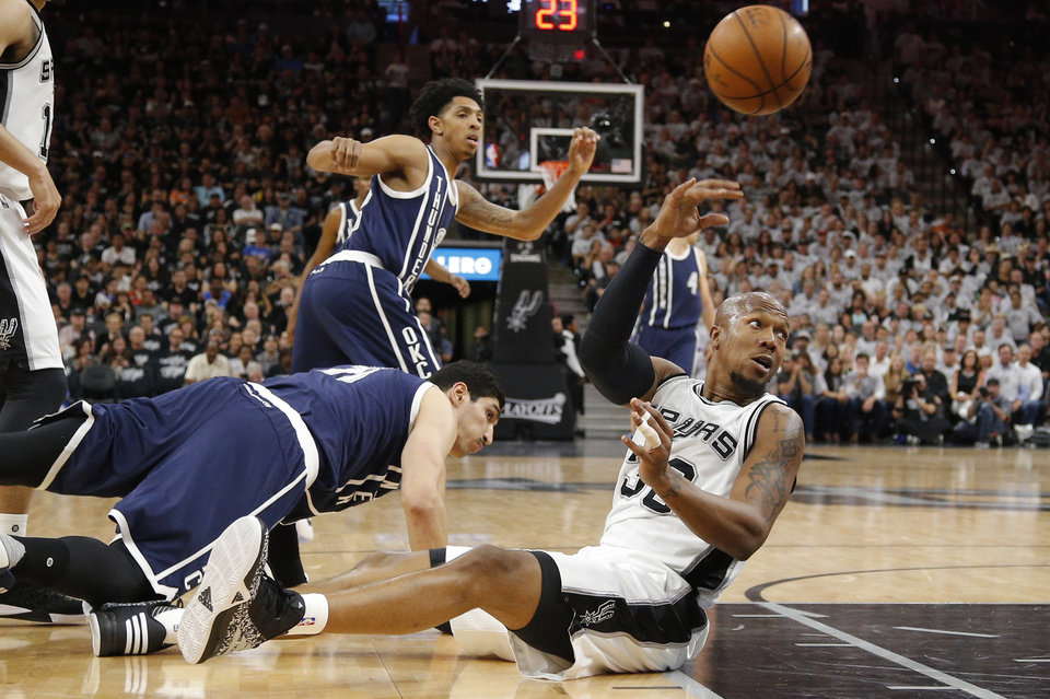 Photo - San Antonio's David West (30) passes the ball from beside Oklahoma City's Enes Kanter (11) during Game 1 of the second-round series between the Oklahoma City Thunder and the San Antonio Spurs in the NBA playoffs at the AT&T Center in San Antonio, Saturday, April 30, 2016. San Antonio won 124-92. Photo by Bryan Terry, The Oklahoman