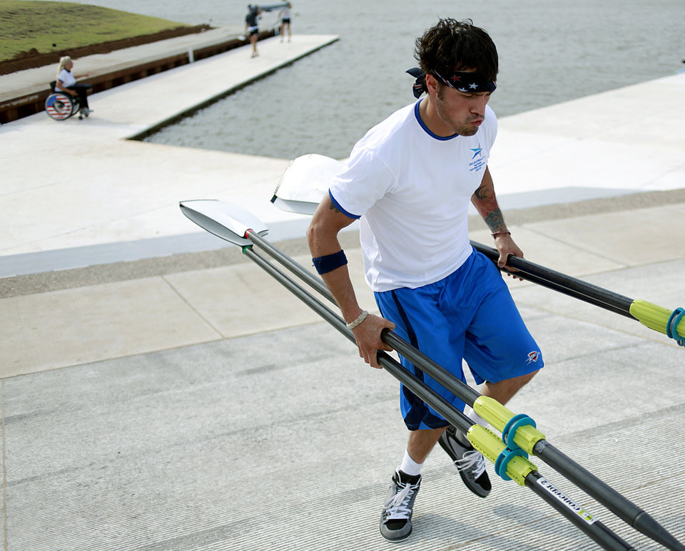 Photo - Tony Davis carries his oars toward the Devon Boathouse after practice with rowing partner Jacqui Kapinowski on the Oklahoma River in Oklahoma City on Tuesday, June 14, 2011. A car accident left Davis, a former Navy Rescue Diver, paralyzed. He taught himself to walk with difficulty, and has been rowing for two years.  Photo by John Clanton, The Oklahoman
