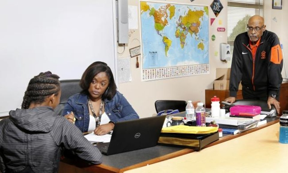 Photo -  Douglass High School student Keosha Jackson talks with her teacher Mauri Hubbard as Mauri's father and fellow teacher Robert Hubbard looks on at the northeast Oklahoma City school. [Jim Beckel/The Oklahoman]