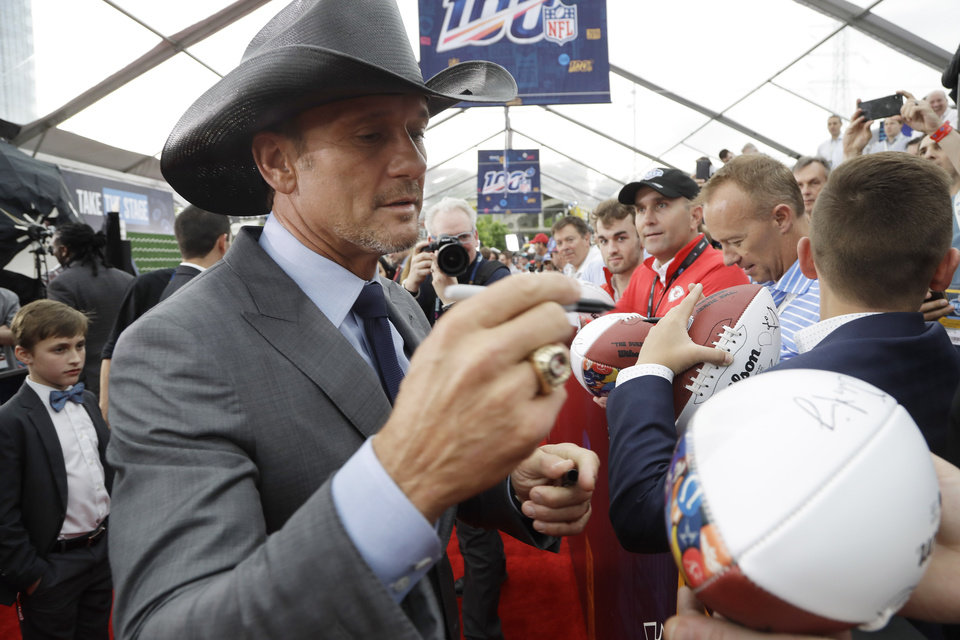 Photo - Country music star Tim McGraw signs an autograph as he walks the red carpet ahead of the first round at the NFL football draft, Thursday, April 25, 2019, in Nashville, Tenn. (AP Photo/Steve Helber)