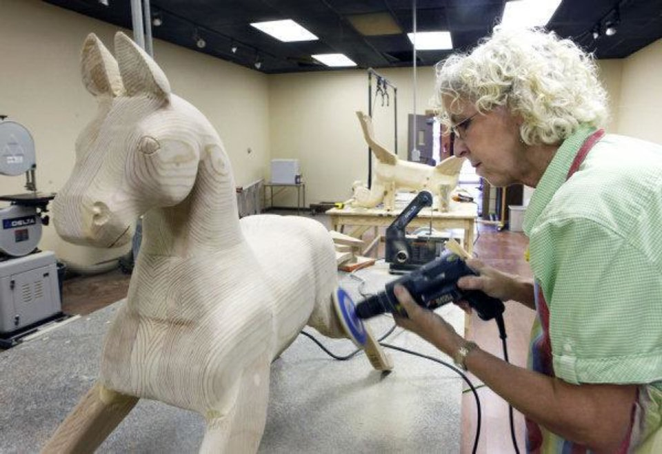 Photo - Jackie Wilson sands a rocking horse at her new shop in downtown Edmond. PHOTO BY PAUL HELLSTERN, THE OKLAHOMAN  PAUL HELLSTERN